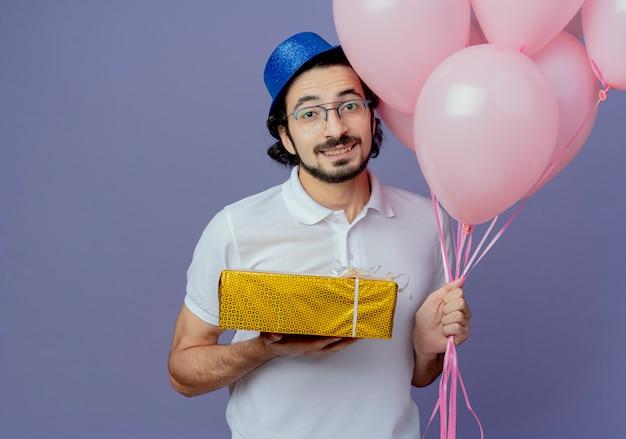 Lächelnder gutaussehender mann, der brille und blauen hut trägt, der luftballons und geschenkbox lokalisiert auf purpur hält