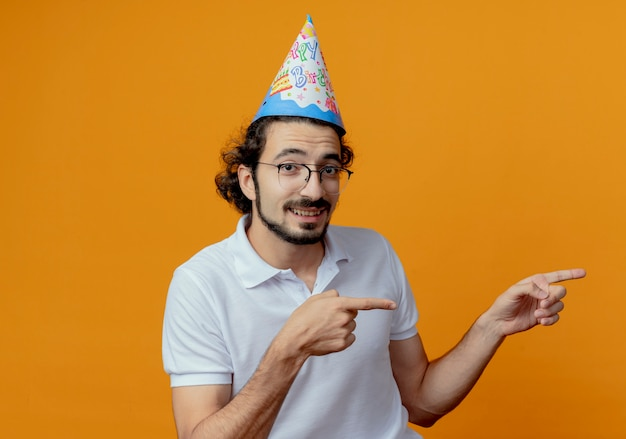 Lächelnder gutaussehender mann, der brille und geburtstagskappenpunkte an der seite trägt, lokalisiert auf orange hintergrund mit kopienraum