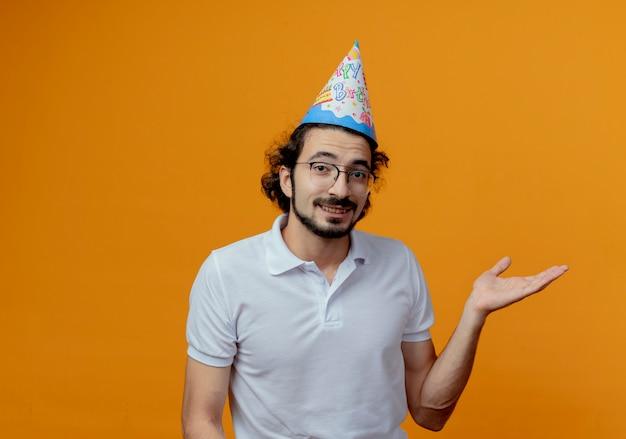 Lächelnder gutaussehender mann, der brille und geburtstagskappenpunkte mit hand zur seite lokalisiert auf orange hintergrund mit kopienraum trägt