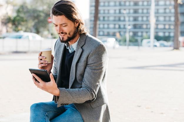 Lächelnder gutaussehender mann, der den handy hält wegwerfkaffeetasse betrachtet