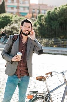 Lächelnder gutaussehender mann, der die mitnehmerkaffeetasse spricht am handy im park hält