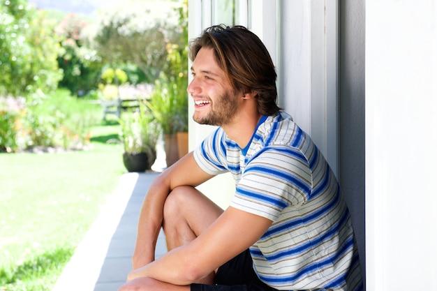 Lächelnder gutaussehender mann, der draußen auf patio sitzt