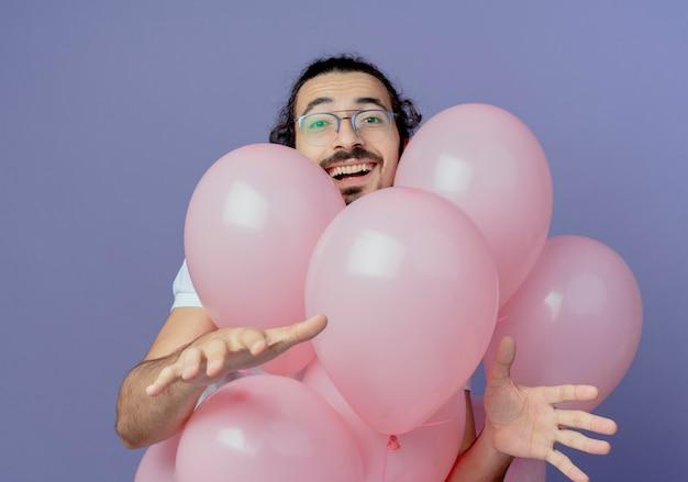 Lächelnder gutaussehender mann, der eine brille trägt, die hinten an luftballons steht und hände spaltet, die auf purpur isoliert werden