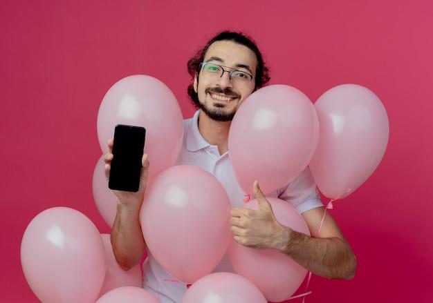 Lächelnder gutaussehender mann, der eine brille trägt, die hinter luftballons steht, die telefon seinen daumen oben lokalisiert auf rosa wand halten