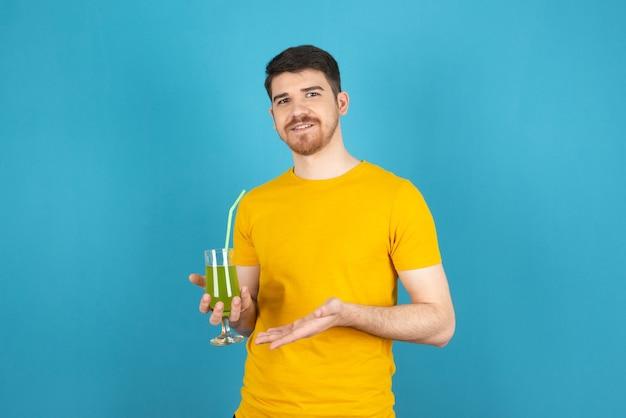 Lächelnder gutaussehender mann, der frischen cocktail hält und die kamera auf einem blau betrachtet.