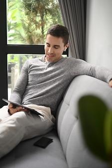 Lächelnder gutaussehender mann, der im wohnzimmer sitzt und digitale tablette verwendet.
