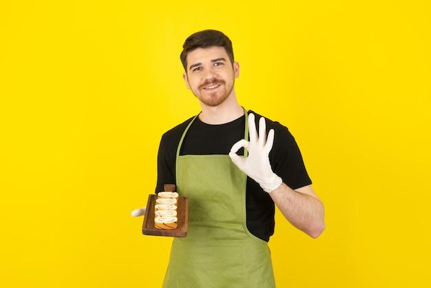 Lächelnder gutaussehender mann, der kuchenrollen hält und ok gestikuliert.