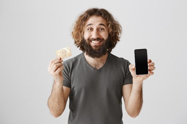 Lächelnder gutaussehender mann, der smartphone-app auf bildschirm und kreditkarte zeigt