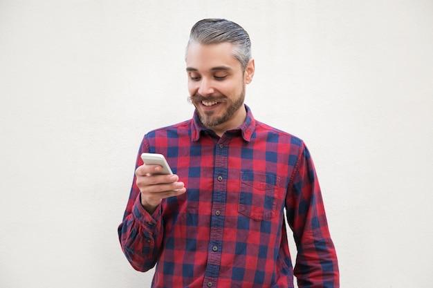 Lächelnder gutaussehender mann, der smartphone verwendet