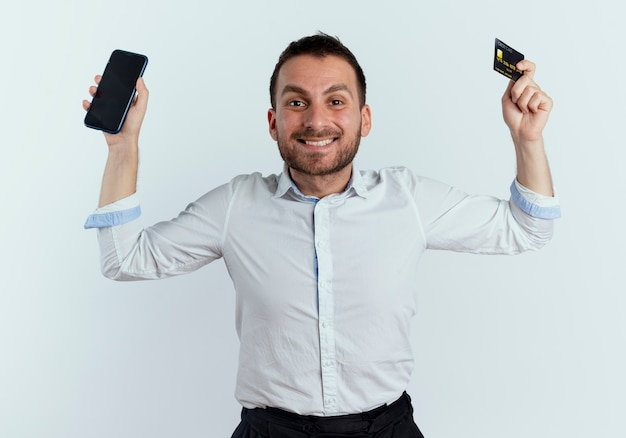 Lächelnder gutaussehender mann erhebt hände, die telefon und kreditkarte lokalisiert auf weißer wand halten