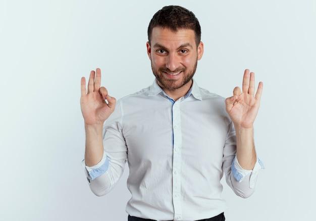Lächelnder gutaussehender mann gestikuliert ok handzeichen lokalisiert auf weißer wand