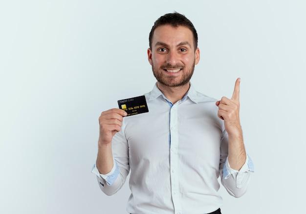 Lächelnder gutaussehender mann hält kreditkarte und zeigt isoliert auf weißer wand