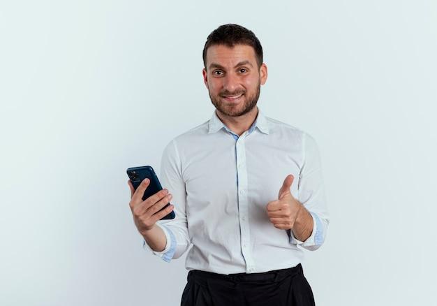 Lächelnder gutaussehender mann hält telefon und daumen isoliert auf weißer wand