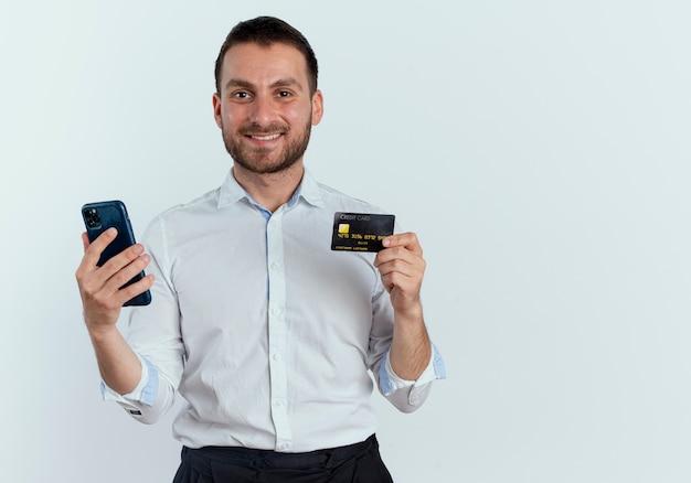 Lächelnder gutaussehender mann hält telefon und kreditkarte lokalisiert auf weißer wand
