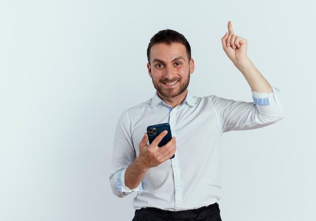 Lächelnder gutaussehender mann hält telefon und zeigt isoliert auf weiße wand