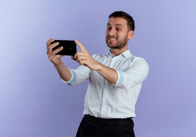 Lächelnder gutaussehender mann hält und betrachtet telefon lokalisiert auf lila wand