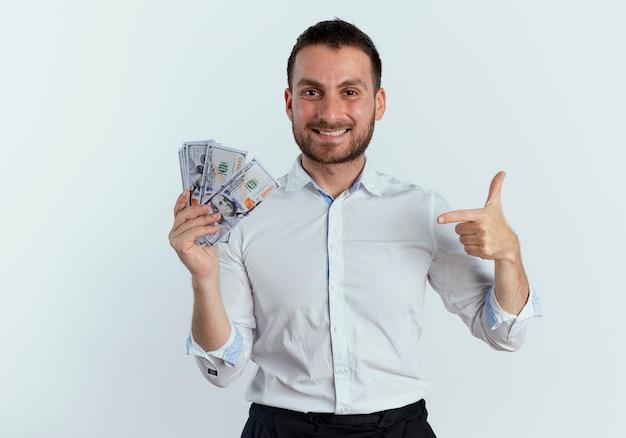 Lächelnder gutaussehender mann hält und zeigt auf geld, das auf weißer wand isoliert wird