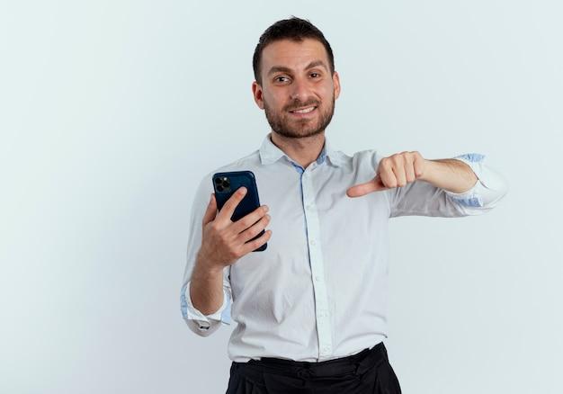 Lächelnder gutaussehender mann hält und zeigt auf telefon, das isoliert auf weißer wand schaut