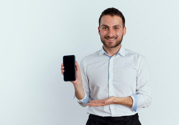 Lächelnder gutaussehender mann hält und zeigt auf telefon mit hand lokalisiert auf weißer wand