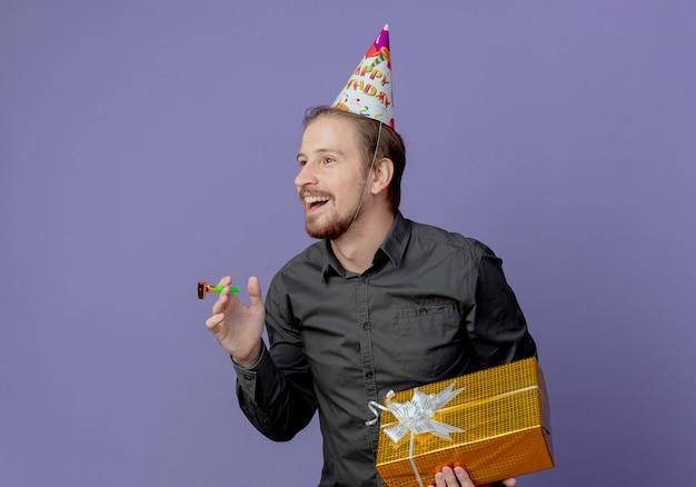 Lächelnder gutaussehender mann in der geburtstagskappe hält geschenkbox und pfeife, die die seite lokalisiert auf lila wand betrachtet