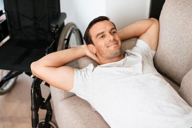 Lächelnder gutaussehender mann liegt auf sofa near wheelchair.