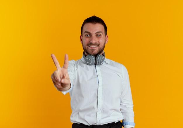 Lächelnder gutaussehender mann mit kopfhörern am hals gestikuliert siegeshandzeichen lokalisiert auf orange wand