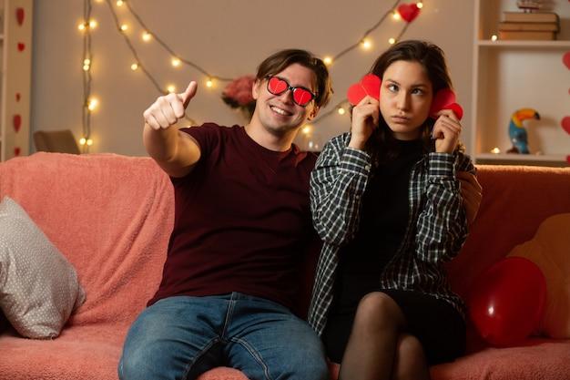 Lächelnder gutaussehender mann mit roter herzförmiger brille, der auf der couch sitzt, mit einer lustigen jungen frau, die am valentinstag rote herzformen im wohnzimmer hält