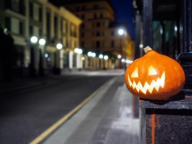 Lächelnder halloween-kürbis auf einer einsamen stadtstraße in der nacht