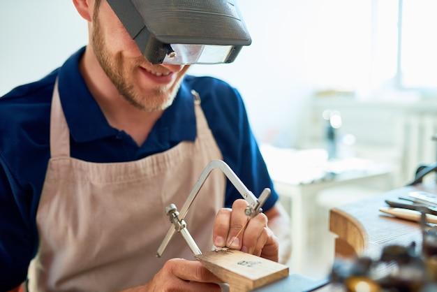 Lächelnder handwerker, der ringe in der werkstatt macht