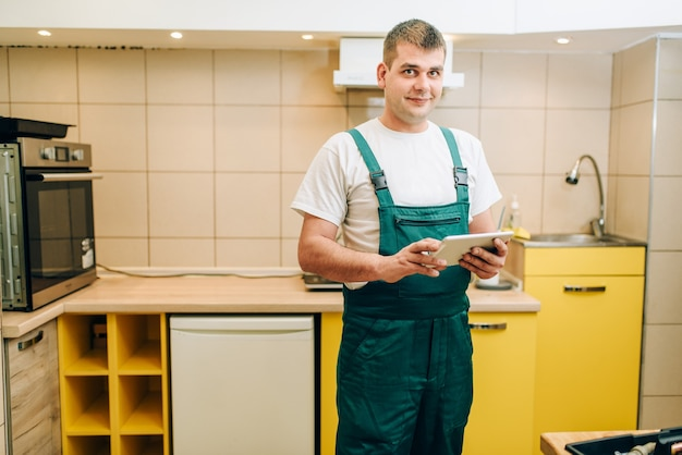 Lächelnder handwerker in uniform hält laptop, handwerker