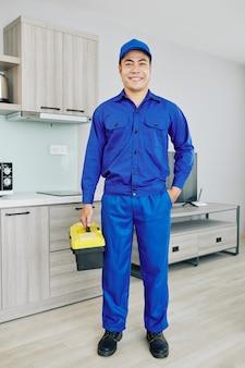Lächelnder handwerker mit werkzeugkasten