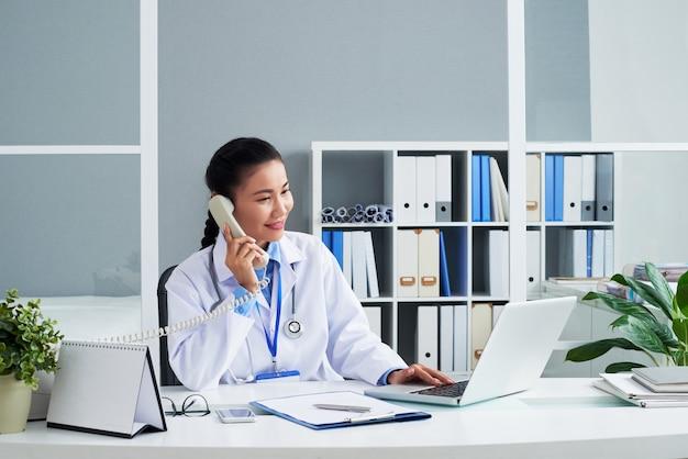 Lächelnder hausarzt, der mit dem patienten telefoniert und e-mails mit seinen beschwerden liest und...