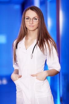 Lächelnder hausarzt mit einem stethoskop. gesundheitswesen. junge frau. doktorandin. in einer medizinischen einrichtung. weiße robbe.