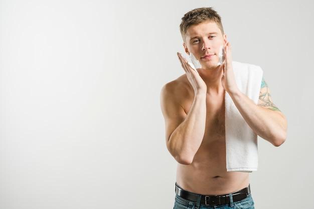 Lächelnder hemdloser junger mann, der schaum auf seiner backe lokalisiert auf grauem hintergrund rasiert zutrifft