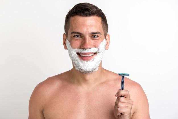 Lächelnder hemdloser junger mann mit angewendetem schaum und dem halten des rasiermessers, das gegen weißen hintergrund steht