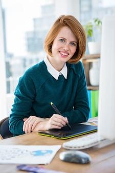 Lächelnder hippie-designer, sitzend an ihrem schreibtisch, auf einem digitalen tablet