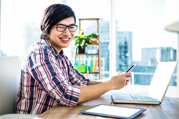 Lächelnder hippie-geschäftsmann unter verwendung des smartphone im büro