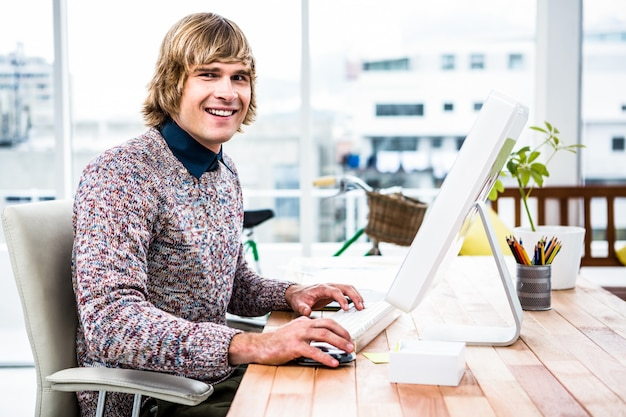 Lächelnder hippie-geschäftsmann unter verwendung seines computers im büro