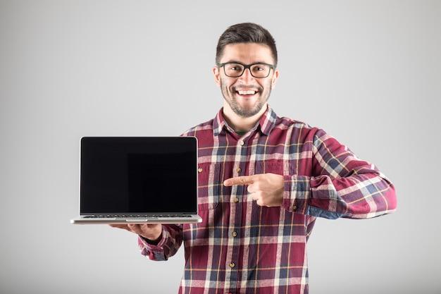 Lächelnder hipster, der finger auf leerem laptop-bildschirm zeigt