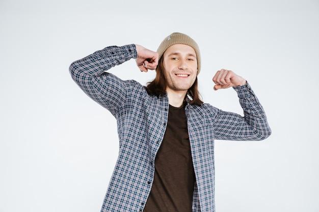 Lächelnder hipster zeigt seinen bizeps
