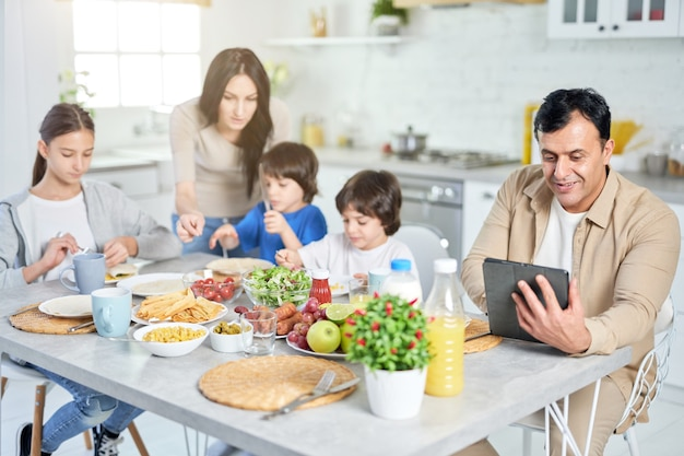 Lächelnder hispanischer vater mit digitalem tablet, während er zusammen mit seiner familie zu mittag isst und zu hause am küchentisch sitzt. glückliche familie, technologiekonzept. selektiver fokus