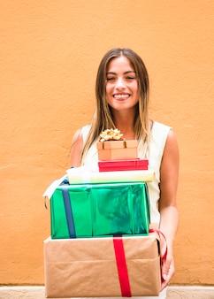 Lächelnder holdingstapel der jungen frau geschenke gegen orange wand