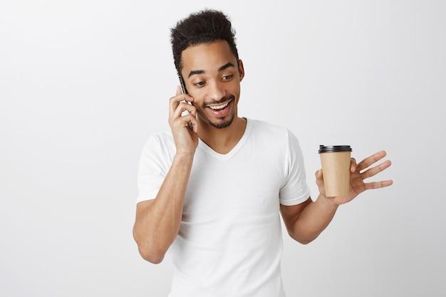 Lächelnder hübscher afroamerikanermann, der am telefon spricht und kaffee mit glücklichem ausdruck trinkt