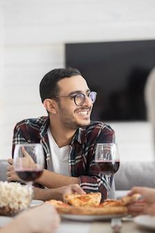 Lächelnder hübscher arabischer kerl in den gläsern, die am tisch im wohnzimmer sitzen und mit freunden plaudern