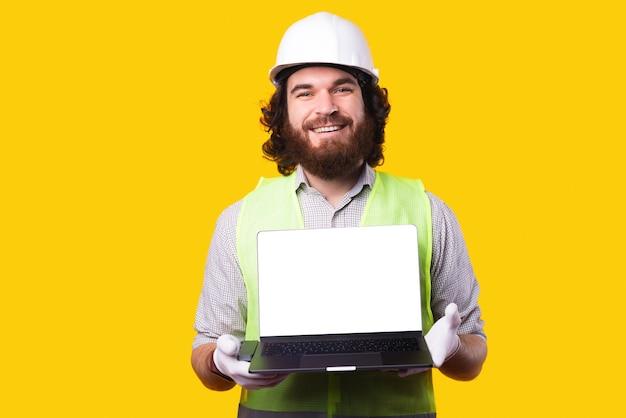 Lächelnder hübscher architektenmann, der weißen leeren bildschirm des laptops zeigt
