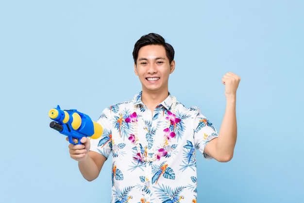 Lächelnder hübscher asiatischer mann, der mit wasserpistole spielt und seine faust für songkran festival in thailand und südostasien erhebt