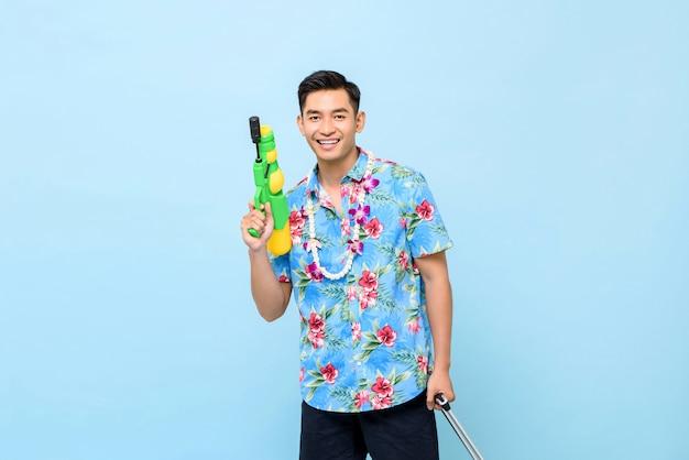 Lächelnder hübscher asiatischer mann, der mit wasserpistole während des songkran-festivals in thailand und in südostasien spielt