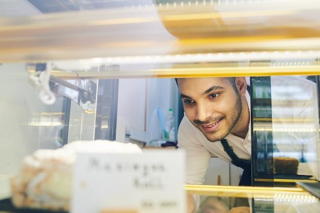 Lächelnder hübscher barista, der ein stück leckeren kuchens vom schaufenster für kunden nimmt