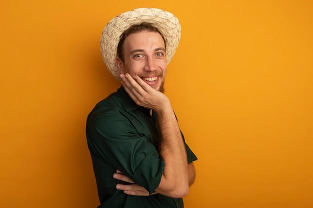 Lächelnder hübscher blonder mann mit strandhut legt hand auf gesicht lokalisiert auf orange wand