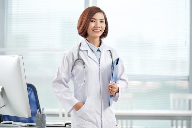 Lächelnder hübscher doktor, der im krankenhausbüro mit einem papierordner steht